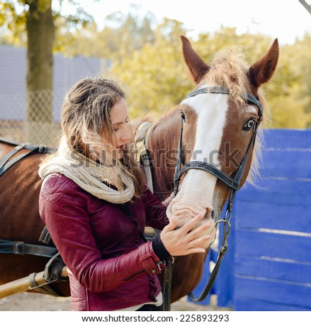portrait of elegant beautiful young woman embracing horse smiling on autumn copy space outdoors background