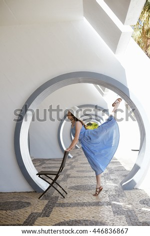 Portrait of elegant beutiful female dancing with chair, sunny rays archway background