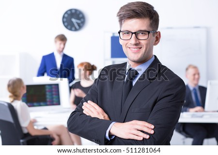 Portrait of elegant boss with his arms folded and other employees at office