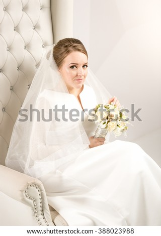 Portrait of elegant bride with white roses sitting on chair at studio