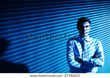 Portrait of elegant businessman looking at camera with blind shades on background - stock photo