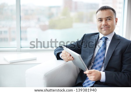 Portrait of elegant businessman with touchpad sitting in office - stock photo