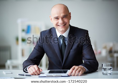 Portrait of elegant businessman with touchpad working in office - stock photo