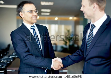 Portrait of elegant businessmen handshaking in conference hall - stock photo