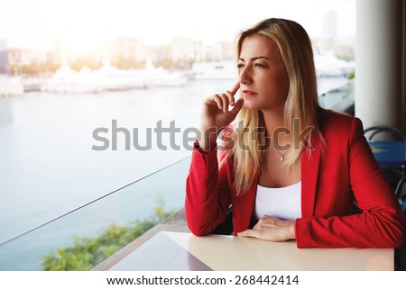 Portrait of elegant businesswoman sitting at outdoors coffee shop looking serious and thoughtful, young blonde woman looking thoughtfully with marina port view on background - stock photo