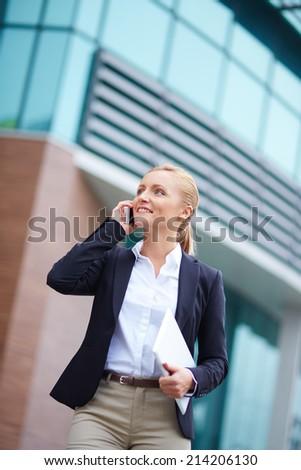 Portrait of elegant businesswoman speaking on the cellular phone outside - stock photo