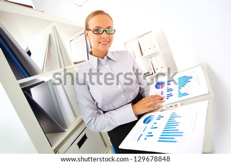 Portrait of elegant businesswoman with papers looking at camera in office - stock photo