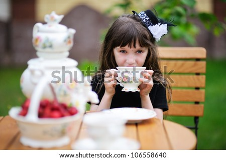 Portrait of elegant child girl in a black dress having a tea party outdoors, focus on the background with girl's face - stock photo