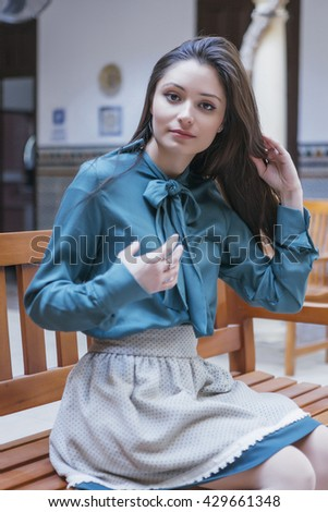 Portrait of elegant dark-haired woman sitting on bench and looking calmly at camera