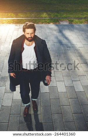 Portrait of elegant fashionable adult man dressed in coat walking in urban setting, stylish hipster man walking on the street at sunny evening, filter and flare sun - stock photo