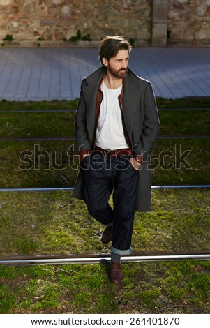 Portrait of elegant fashionable adult man dressed in coat walking on tram-line in urban setting, stylish hipster man walking on the street at sunny evening - stock photo