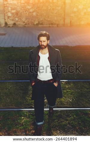 Portrait of elegant fashionable adult man dressed in coat walking on tram-line in urban setting, stylish hipster man walking on the street at sunny evening, flare sunshine - stock photo