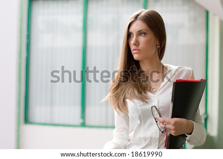 Portrait of elegant female with documents and eyeglasses in hand looking aside outdoors