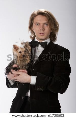 Portrait of elegant gentleman holding his cute yokshire terrier, studio image - stock photo