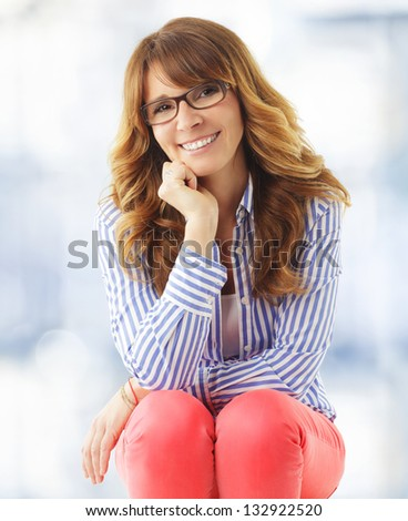 Portrait of elegant middle aged ( mature ) woman smiling in living room. - stock photo