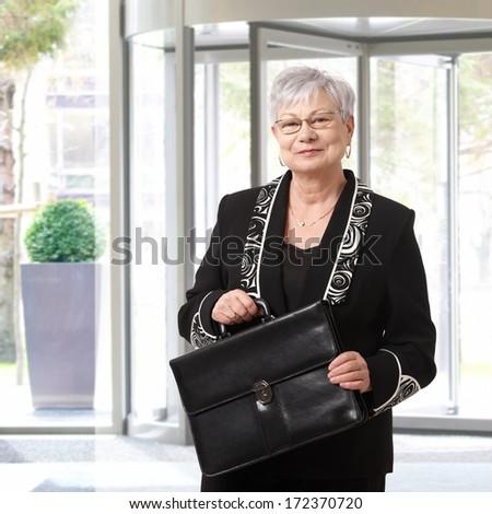 Portrait of elegant senior businesswoman holding briefcase. - stock photo