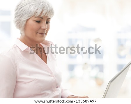 Portrait of elegant senior woman working with laptop in living room.