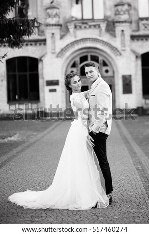 Portrait of elegant wedding couple near the old building