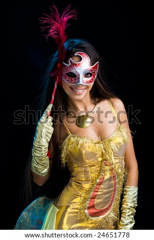 Portrait of elegant woman in yellow apparel with venetian mask in hand - stock photo