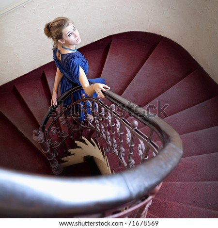 Portrait of elegant woman on circular staircase - stock photo