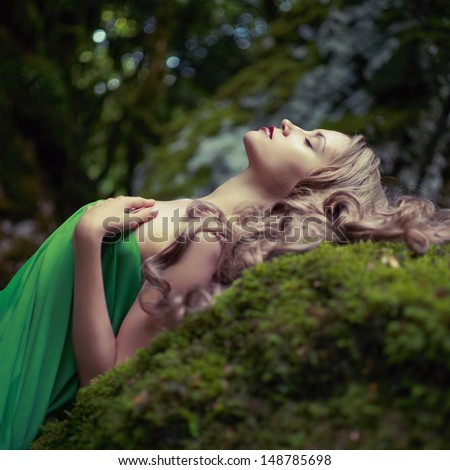Portrait of elegant woman with luxurious hair in a coniferous forest - stock photo