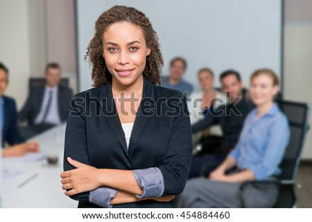 Portrait of elegant young businesswoman with team sitting at office desk on background
