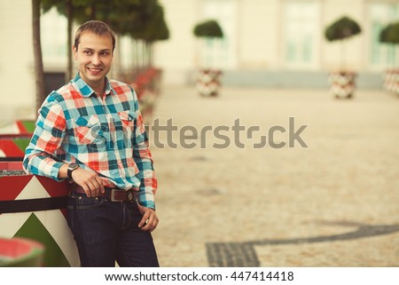 Portrait of elegant young man in trendy clothing waiting for friends, date in park. Casual street style clothes. Copy-space. Outdoor shot - stock photo