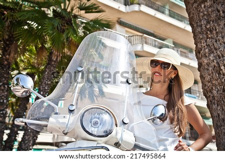 Portrait of elegant young woman near scooter - Outdoor on street. Retro shot. Fashion colors. (focus on motorcycle) - stock photo