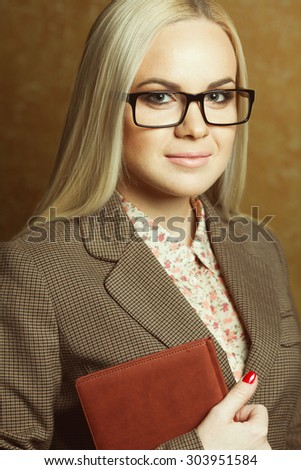 Portrait of elegantly dressed young gorgeous blonde woman in trendy eyewear holding leather notebook posing over golden background. Smart casual style. Natural make-up. Close up. Studio shot