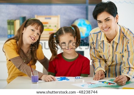 Portrait of elementary age children and teacher in art class in primary school classroom. Looking at camera, smiling. - stock photo