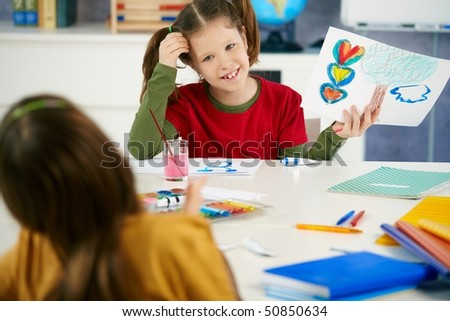 Portrait of elementary age schoolgirl showing colorful paining to classmate in art class in primary school classroom. - stock photo