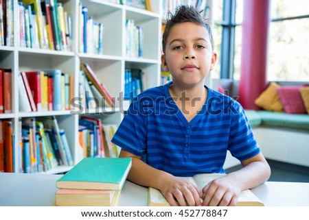 Portrait of elementary boy reading book at table in school library
