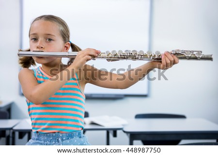 Portrait of elementary girl playing flute while sitting on desk in classroom - stock photo
