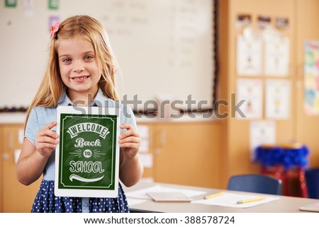Portrait of elementary school girl holding a smart tablet - stock photo