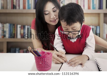 Portrait of elementary school student learn to write with his mother. shot in the library