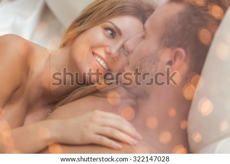 Portrait of embracing amorous couple lying in bed