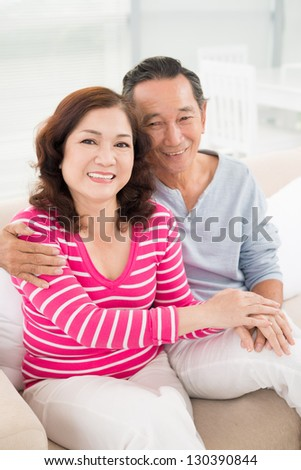 Portrait of embracing seniors looking at camera - stock photo