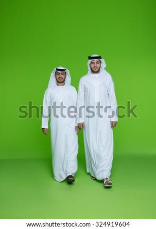 Portrait of Emirati businessmen walking - stock photo