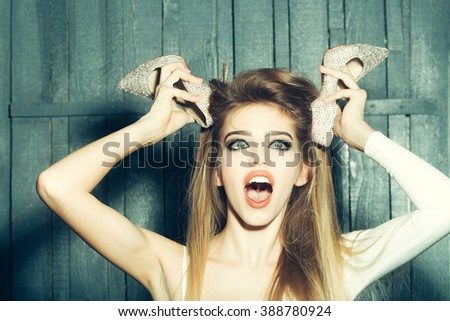 Portrait of emotional crazy glamour fashion young girl with long beautiful hair holding shoes in raised hands near face on wooden background, horizontal picture - stock photo