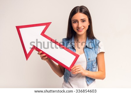 Portrait of emotional girl teenager with paper arrow on a white background