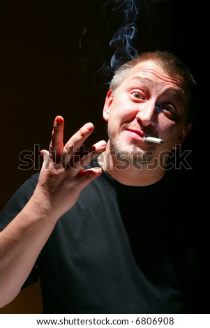 Portrait of emotional man with cigarette over black background