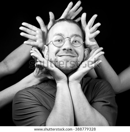 portrait of emotional young man and lot of hands - stock photo