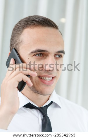 Portrait of employee talking on mobile phone in office