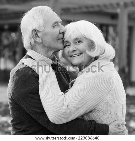 Portrait of endless love. Black and white portrait of happy senior couple bonding to each other and smiling while standing outdoors and in front of their house  - stock photo