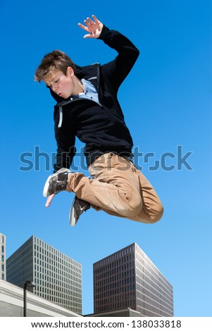 Portrait of energetic boy jumping high in city.