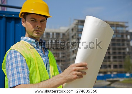 Portrait of engineer holding blueprint at construction site - stock photo