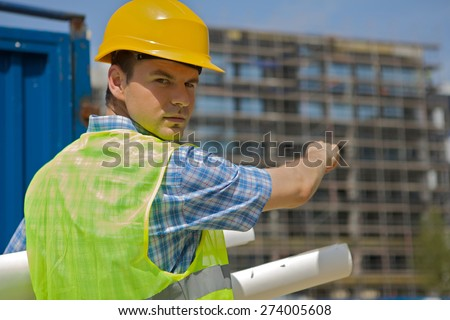 Portrait of engineer holding blueprint on construction site - stock photo