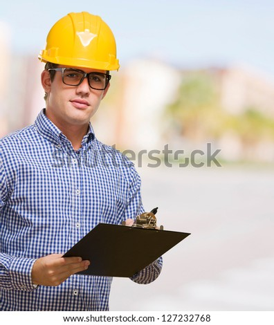 Portrait Of Engineer Holding Clipboard against a street background - stock photo