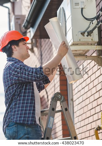 Portrait of engineer in hardhat looking in plan of air conditioning system