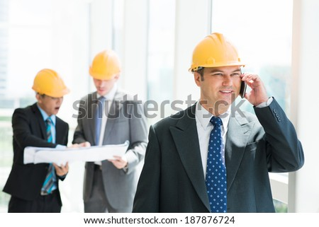 Portrait of engineer speaking on the phone on the foreground - stock photo